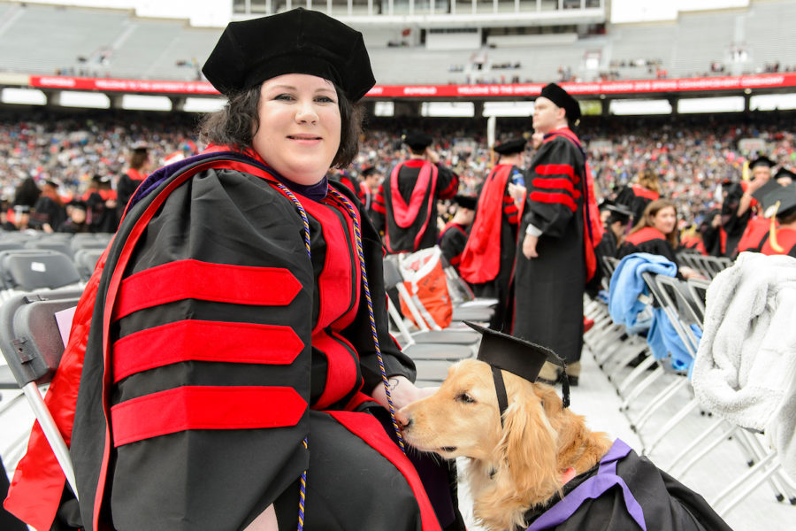 student and her service dog at commencement ceremony in cap and gown