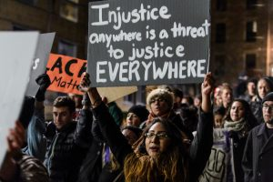student holds sign at a rally saying injustice anywhere is a threat to justice everywhere