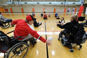 athletes in wheelchairs play indoor volleyball